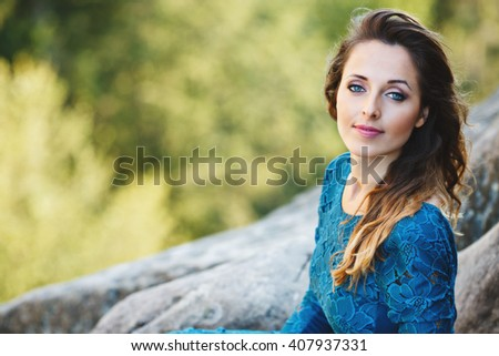 Girl sitting near rocks, outdoor. Looking at camera, hair on one side, turning a little bit aside, smiling. Woman wearing blue dress, nice make up. Waist up, closeup, copyspace  - stock photo