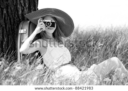 Girl sitting near tree with vintage camera. Photo in old yellow color image style. - stock photo