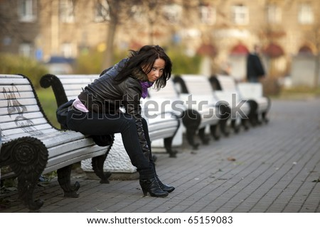 Girl sitting on a bench in the street - stock photo