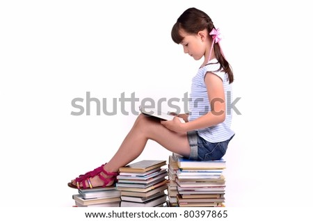 Girl sitting on a big pile of books and reading isolated on white background - stock photo