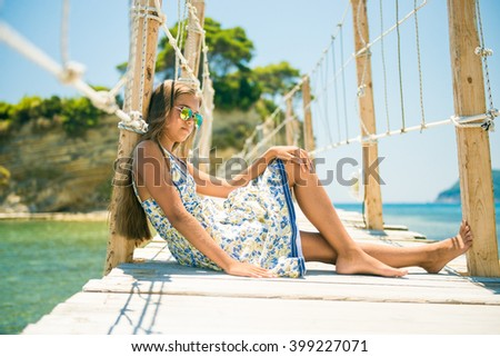 girl sitting on a bridge. beautiful teen girl in a dress with long hair and sunglasses sitting on the bridge in summer