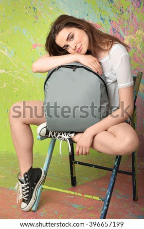 Girl sitting on a chair in the Studio and hugs your backpack - stock photo