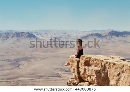 Girl sitting on a cliff and looking at desert Negev landscape. Summer vacation in Israel.