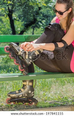 Girl sitting on a park bench while checking her rollers.