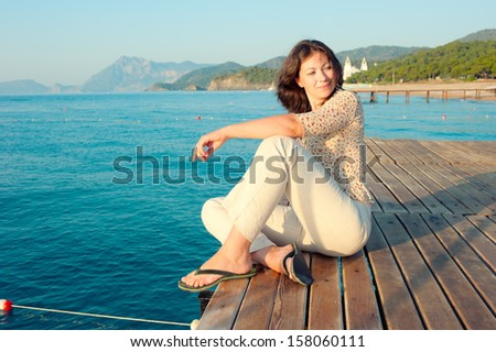 girl sitting on a pier near the sea and looking to the side - stock photo