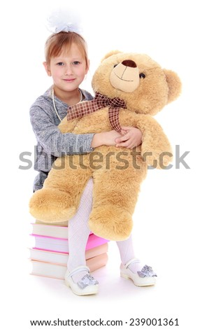 Girl sitting on a pile of books and holding a teddy bear. Studio photo, isolated on white background. - stock photo