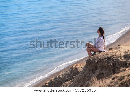 Girl sitting on a rock and looking at sea