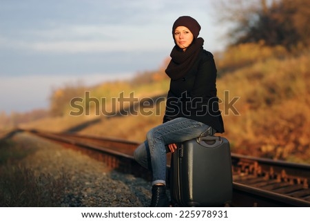 girl sitting on a suitcase along the  train tracks - stock photo