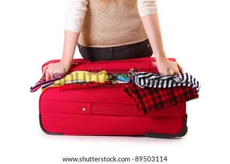 Girl sitting on a suitcase and tries close it isolated on a white - stock photo