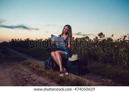 Girl sitting on a suitcase in a sunflower field. Sunset.