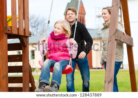 Girl sitting on a swing, father on mother pushing - stock photo