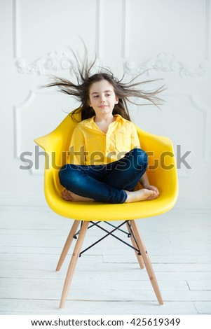 girl sitting on a yellow chair with hair flaring fashion portrait of beautiful little girl with healthy hair