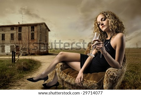 girl sitting on armchair with glass of wine in the countryside - stock photo