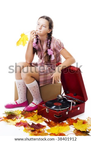 Girl sitting on box and waiting with gramophone and maple leafs, isolated on white - stock photo