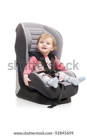 girl sitting on child's car seat - isolated on a white background - stock photo