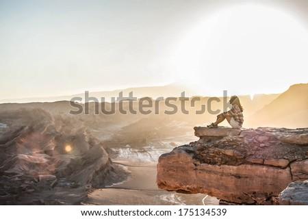 Girl sitting on cliff edge - stock photo