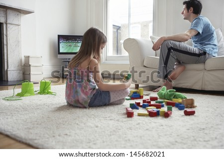 Girl sitting on floor and playing with blocks while father watching television at home - stock photo