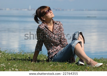 Girl sitting on grass and taking the sun. There are sea and the city in the background - stock photo
