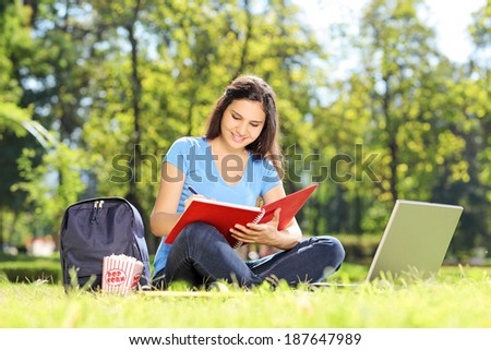 Girl sitting on grass and writing in a notebook outdoors - stock photo