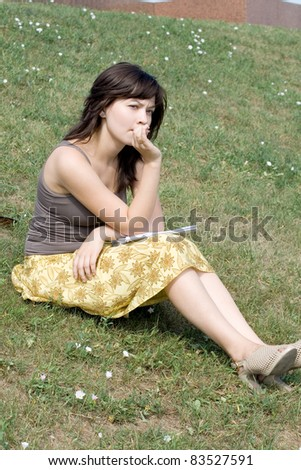 Girl sitting on grass in park - stock photo