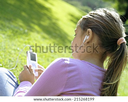 Girl sitting on grass in park, listening to MP3 player, rear view, close-up (tilt) - stock photo