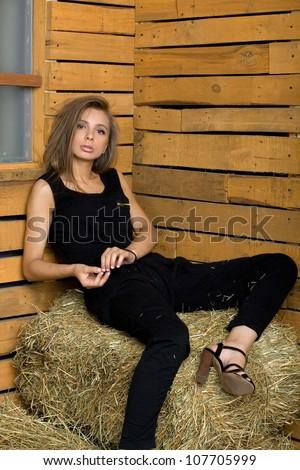 Girl sitting on hay - stock photo