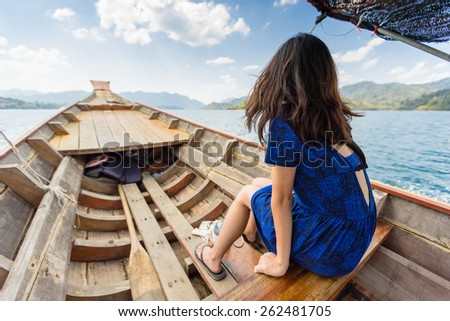 Girl sitting on old wooden longtail boat in Cheow Lan lake of Khao Sok National park admiring the view of mountains in the distance - stock photo