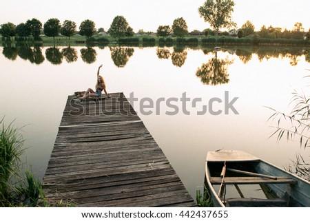 Girl sitting on pier - stock photo