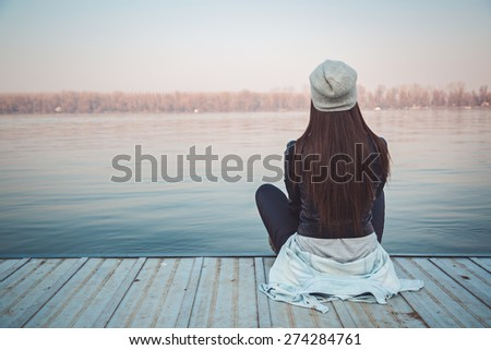 Girl sitting on pier and lookingat the river - stock photo