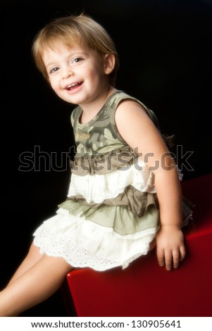 Girl sitting on red bench with dress camouflage. - stock photo
