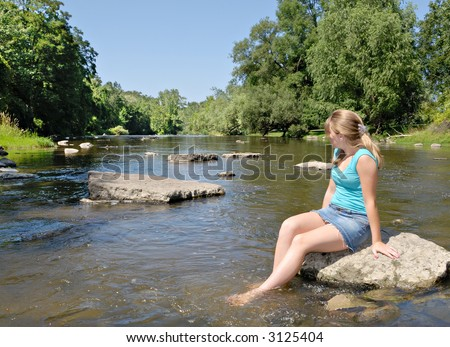 Girl sitting on rock in creek soaking her feet and enjoying the view - stock photo