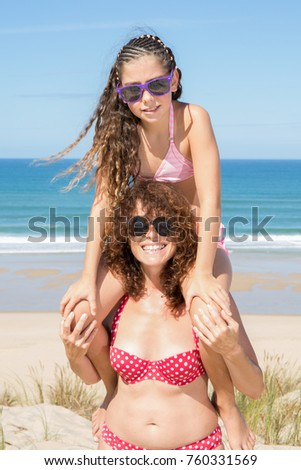 Girl sitting on shoulders of mother