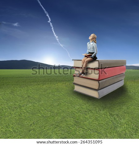 girl sitting on stack of books and reading book - stock photo