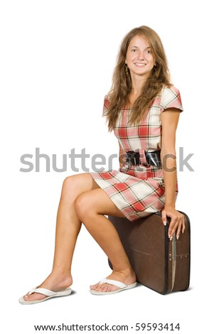 Girl sitting on suitcase. Isolated over white background