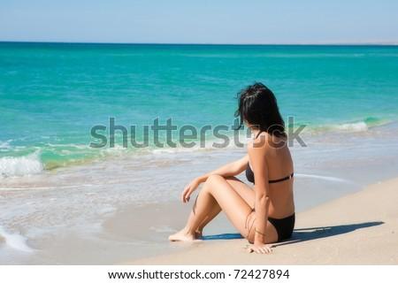 Girl sitting on the beach - stock photo
