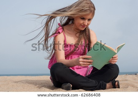 Girl sitting on the beach and reading a book - stock photo