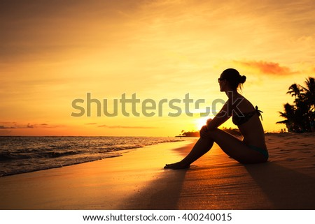 Girl sitting on the beach at sunset.