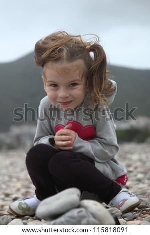 Girl sitting on the beach in high winds with developing hair - stock photo