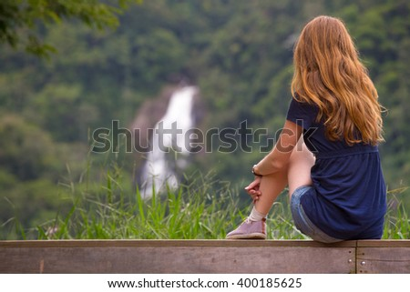 girl sitting on the bench and waterfall at the background, cachoeira do pacau, santa rita de jacutinga, Brazil