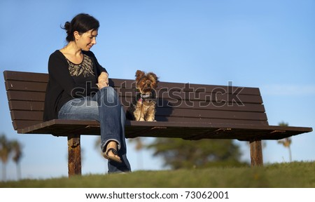 Girl sitting on the bench with her dog - stock photo