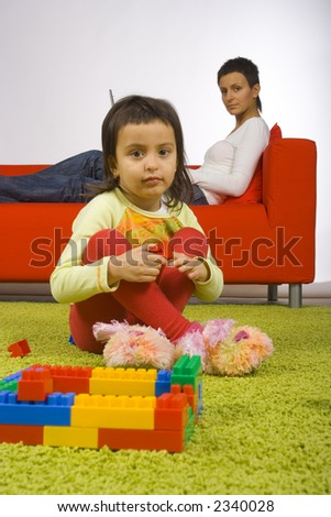 girl sitting on the carpet and playing is watching by her busy (with laptop) mother - stock photo