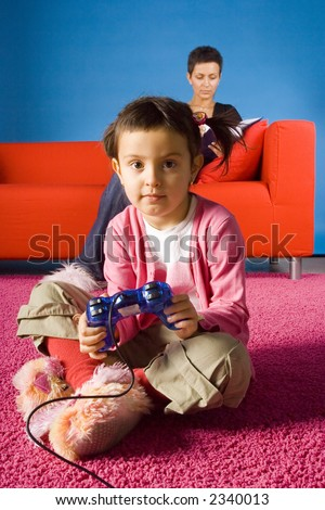 girl sitting on the carpet and playing video game and  her busy (with book) mother on the sofa - stock photo