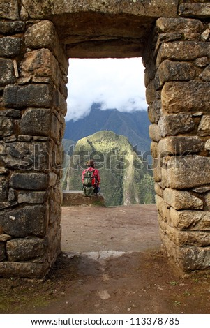 girl sitting on the edge of rock in a stone arch in Machu Picchu, Peru - stock photo