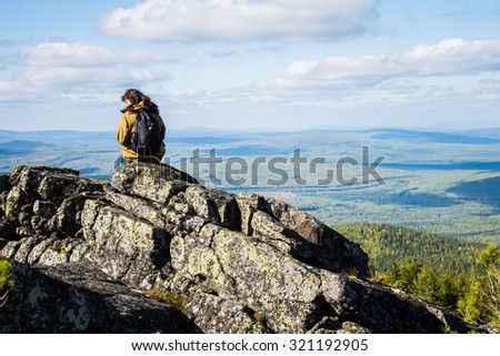 girl sitting on the edge of the mountain and looking into the distance on blue taiga