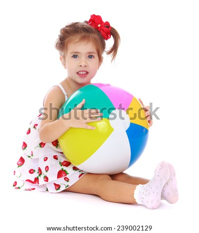 girl sitting on the floor and holding a ball. Studio photo, isolated on white background.