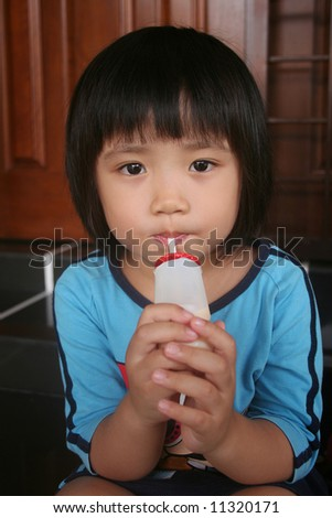 Girl sitting on the floor drinking yogurt