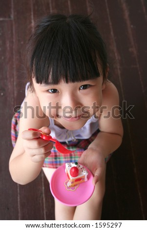 girl sitting on the floor holding toy cake - stock photo