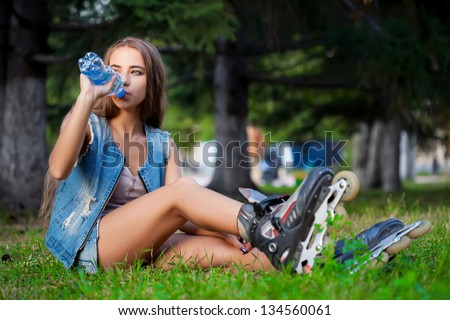 girl sitting on the grass and drinking water from bottle