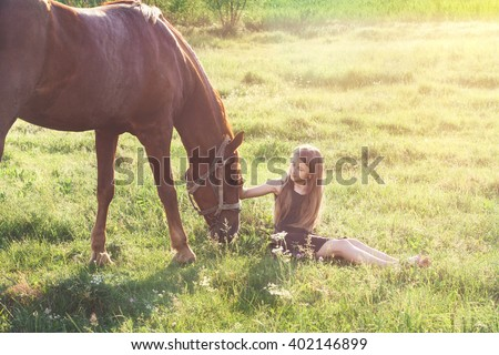 Girl sitting on the grass and stroking her horse - stock photo
