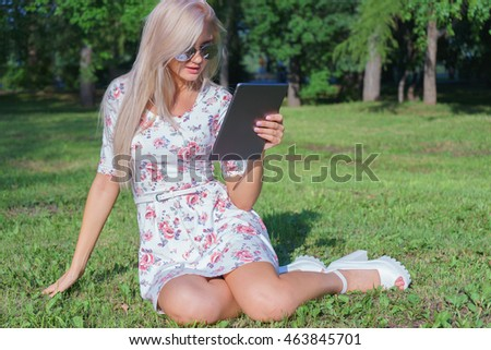 Girl sitting on the grass in the park among the trees and use the Internet on your tablet. Wireless internet connection. Social networking and chat for mobile communication.
